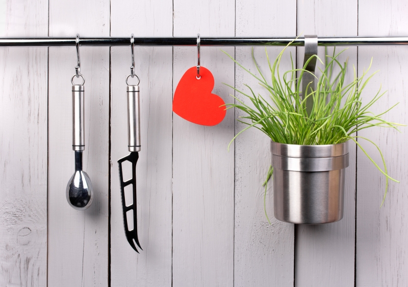 Red heart and kitchen cooking utensil on stainless steel rack. Copy space.